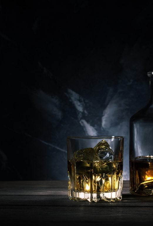 Glass of whiskey with ice, decanter and a wooden barrel